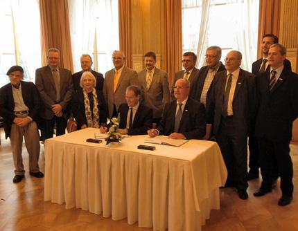 Im Spiegelsaal des Palais Prinz Carl: Werner Pfisterer (5.v.l.) und Martin Ehrbar (6.v.l.) wohnen der Unterzeichnung der Konversionsvereinbarung zwischen der Stadt Heidelberg und der Bundesanstalt für Immobilienaufgaben bei.
